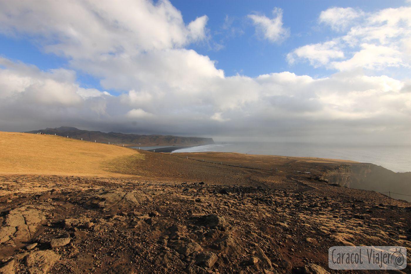 Faro con vistas a la playa de arena negra en Islandia